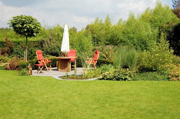 Flere røde havestole og en parasol står i en smuk have